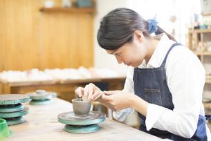 陶芸教室でろくろを回している女性の写真素材 [FYI02661198]