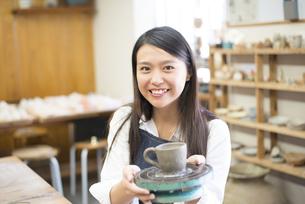 陶芸教室で作品を持って笑っている女性の写真素材 [FYI02661667]