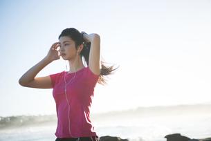 トレーニングウェアで音楽を聴いている女性の写真素材 [FYI02663897]
