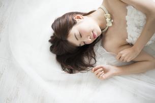 眠っているウェディングドレス姿の女性の写真素材 [FYI02663934]