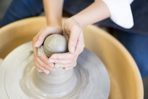 電動ろくろで粘土を触っている女性の手の写真素材 [FYI02663937]