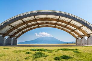 芝生観覧席休憩所アーチ越しに見る雲かかる桜島の写真素材 [FYI02663999]