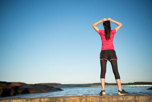 トレーニングウェアでビーチにいる女性の後ろ姿の写真素材 [FYI02664009]