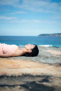 岩場で横たわっている女性の写真素材 [FYI02664012]