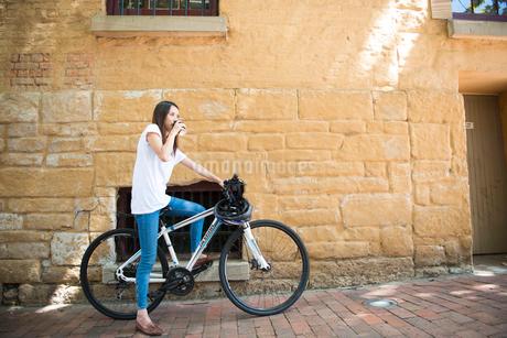 自転車にまたがってコーヒーを飲んでいる女性の写真素材 [FYI02664031]