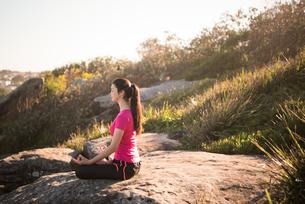 岩の上で瞑想のポーズをしている女性の写真素材 [FYI02664056]