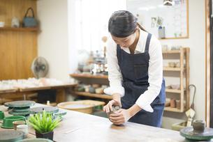 陶芸教室で粘土をこねている女性の手の写真素材 [FYI02664059]