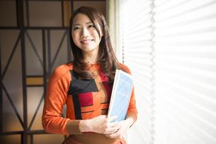 窓辺で楽譜を持って立っている女性の写真素材 [FYI02664061]