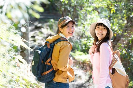 森の中をハイキングしている女性2人の写真素材 [FYI02664063]