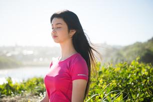 トレーニングウェアで目を瞑っている女性の写真素材 [FYI02664069]