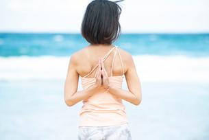 海で後ろ合掌のポーズでヨガをしている女性の写真素材 [FYI02664071]