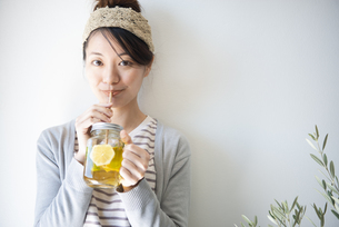 アイスレモンティーを紙ストローで飲んでいる女性の写真素材 [FYI02664074]