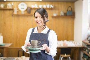 陶芸教室で作品を持って笑っている女性の写真素材 [FYI02664075]