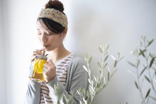 アイスティーを紙ストローで飲んでいる女性の写真素材 [FYI02664079]