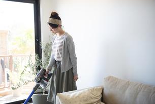 リビングで掃除機をかけている女性の写真素材 [FYI02664081]