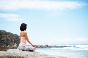 ビーチで瞑想をしている女性の写真素材 [FYI02664090]