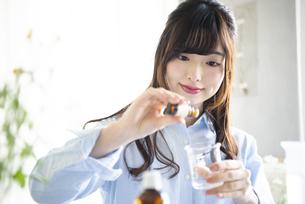 アロマオイルを入れて化粧水を作っている女性の写真素材 [FYI02664091]