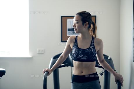 ジムのランニングマシンで休んでいる女性の写真素材 [FYI02664095]