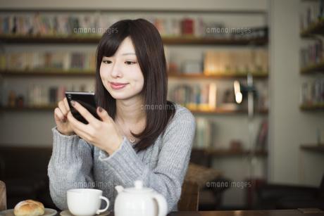 カフェでスマホを見ている女性の写真素材 [FYI02664097]