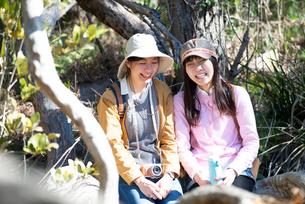 緑の中で座って笑っている女性2人の写真素材 [FYI02664103]