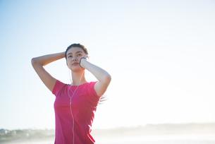 トレーニングウェアで音楽を聴いている女性の写真素材 [FYI02664105]