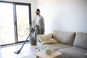 リビングで掃除機をかけている女性の写真素材 [FYI02664108]