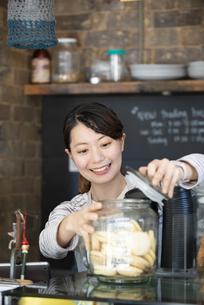 カフェで働いている笑顔の女性店員の写真素材 [FYI02664111]