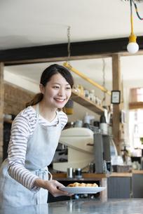 笑顔で接客をしている店員の女性の写真素材 [FYI02664118]