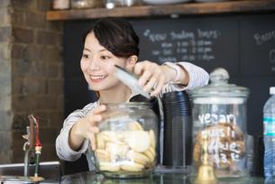 カフェで働いている笑顔の女性店員の写真素材 [FYI02664120]
