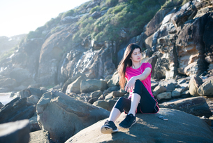 トレーニングウェアで岩の上に座っている女性の写真素材 [FYI02664123]