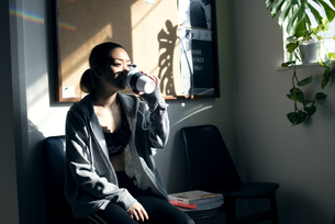 ジムでコーヒーを飲みながら休憩している女性の写真素材 [FYI02664136]