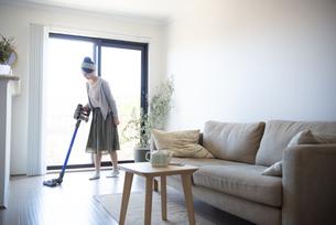 リビングで掃除機をかけている女性の写真素材 [FYI02664139]