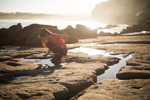 トレーニングウェアで岩場にしゃがんでいる女性の写真素材 [FYI02664142]