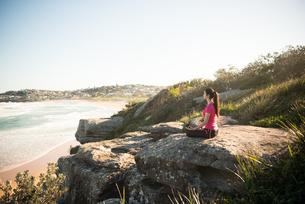 岩の上で瞑想のポーズをしている女性の写真素材 [FYI02664149]