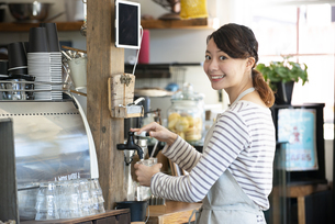カフェで水を汲んでいる笑顔の女性店員の写真素材 [FYI02664156]