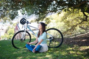 自転車の前で休んでいる女性の写真素材 [FYI02664171]