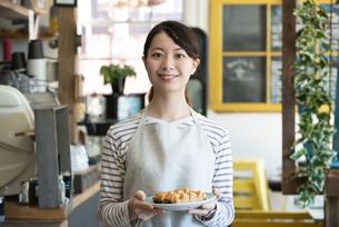 パンを持って笑っている店員の女性の写真素材 [FYI02664175]