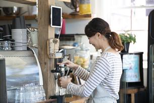 カフェで水を汲んでいる笑顔の女性店員の写真素材 [FYI02664176]