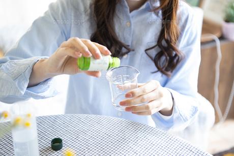 アロマオイルを使って手作り化粧品を作っている女性の写真素材 [FYI02664177]