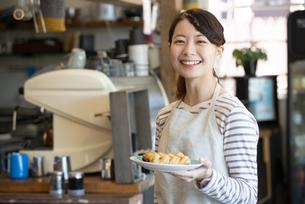 パンを持って笑っている店員の女性の写真素材 [FYI02664188]