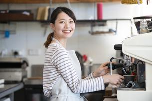 笑顔でエスプレッソマシンを触っている店員の女性の写真素材 [FYI02664190]