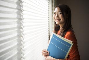 窓辺で楽譜を持って立っている女性の写真素材 [FYI02664191]