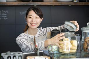 カフェで働いている笑顔の女性店員の写真素材 [FYI02664201]