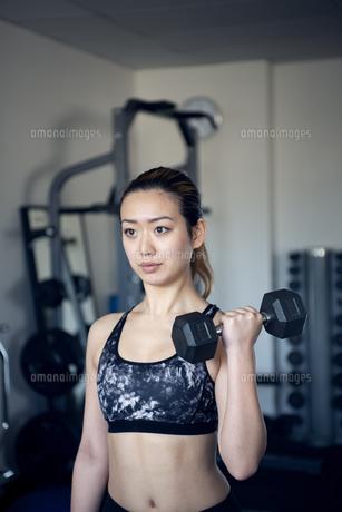 ジムでダンベルを使って筋トレをしている女性の写真素材 [FYI02664233]