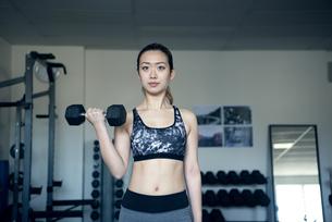 ジムでダンベルを使って筋トレをしている女性の写真素材 [FYI02664252]