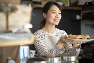 カフェで働いている笑顔の女性店員の写真素材 [FYI02664255]