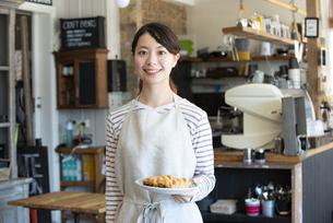 パンを持って笑っている店員の女性の写真素材 [FYI02664259]