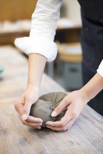 陶芸教室で粘土をこねている女性の手の写真素材 [FYI02664261]