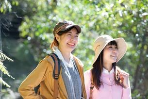 森の中をハイキングしている女性2人の写真素材 [FYI02664262]