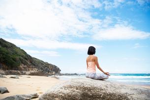 ビーチで瞑想をしている女性の写真素材 [FYI02664275]